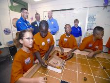 A group of diverse students working together on a project set on Mars, held within a classroom.