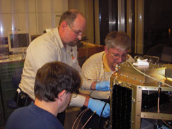 Keith Hogie and Jim Langston assist Dr Smith in the installation of the MidSTAR-1 communications system.