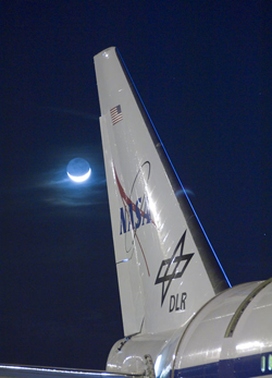Wispy clouds are illuminated by a bright quarter moon behind the tail of NASA's SOFIA flying observatory during telescope characterization testing in March 2008.
