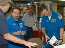 Astronauts Steve Robinson (right) and Charles Camarda (left) inspect the MILT in Discovery Orbiter Processing Facility at KSC