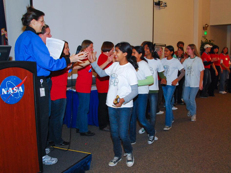 Wendy Holforty, outreach chair of the Women's Influence Network at NASA's Ames Research Center, high fives students at the competition.
