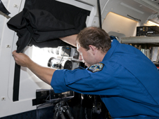 Timothy Marynowski, of the Univseritat Stuttgart, Germany prepares instruments aboard NASA's DC-8 flying laboratory.