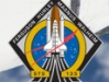 The STS-135 mission patch and the nose of Atlantis.