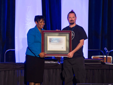 Ames' Matthew Linton poses while accepting the 2012 National Cybersecurity Innovation Award from a representative of the awarding organization.