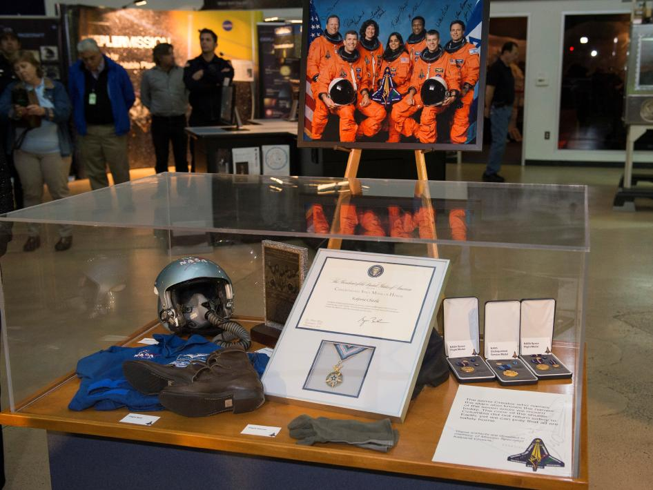 A display case with items that belonged to Kalpana Chawla, including awards and astronaut gear.