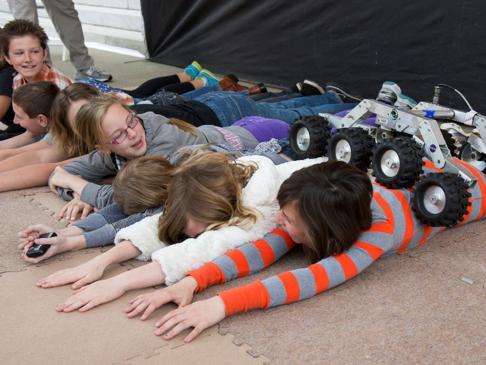 Children laying on the ground simulate the uneven and rocky surface of Mars for a small robotic rover demonstration.