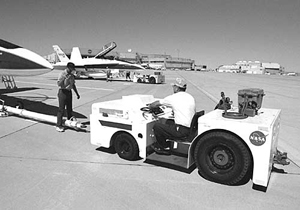 Paul Tremlin and Kevin Mount work carefully to tow an F/A-18.