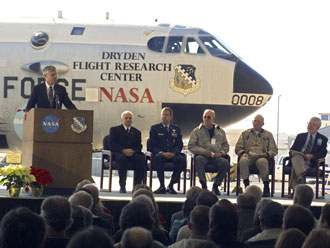 Former Dryden research pilot Ed Schneider takes the podium to share memories about the NB-52B. Also on hand to salute the aircraft were, seated from left, Dryden Center Director Kevin Petersen, Air Force Flight Test Center Commander Brig. Gen. Curtis Bedke, former Dryden pilot Fitzhugh L.