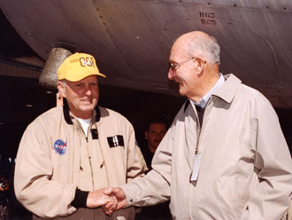 Fullerton, left, and Fulton share a handshake under the fuselage of the venerable aircraft.