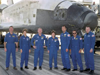The Discovery crew pauses for a photo after giving Discovery her post-landing once-over. From left are Stephen Robinson, Commander Eileen Collins, Andrew Thomas, Wendy Lawrence, Soichi Noguchi, Charles Camarda and Jim Kelly.