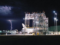 Dryden's Mate/Demate Device was used to raise Discovery and then lower it onto the NASA 747 aircraft that ferried it across the U.S. to Kennedy Space Center, Fla. A summer storm delayed operations, above, illuminating the night sky.