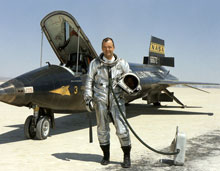 Bill Dana is pictured in his flight suit alongside the legendary rocket plane in which flew to the edge of space.