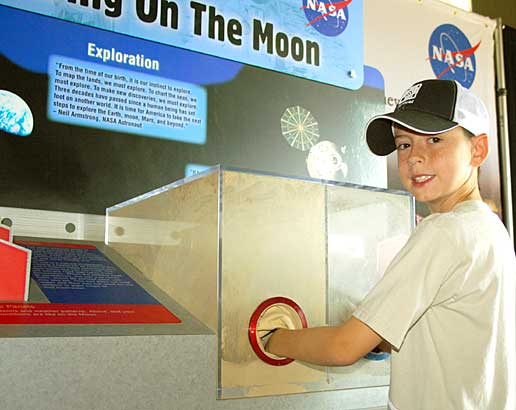 Getting the dirt on exploration, Kyle Wallace of Evansville, Indiana, feels the difference between a soil sample from earth and a replicated batch of moon dust in the NASA exhibit at AirVenture.