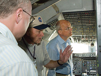 SOFIA chief pilot Gordon Fullerton, center, gives a group of VIP visitors from Germany a tour of the NASA 747SP cockpit.