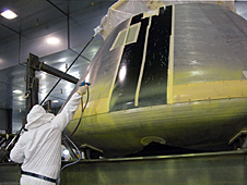 Painter applies the first primer coat to NASA's Orion full-scale abort flight test crew module.