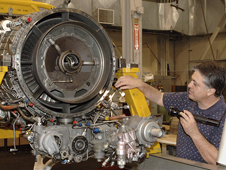 employee inspecting jet engine