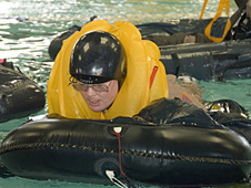 NASA Flight Surgeon Gregg Bendrick practices getting into the one-man life raft during water survival training.