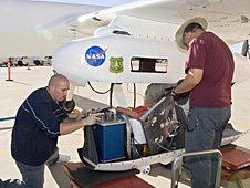 Dryden Ikhana ground crewmen Gus Carreno, left, and James Smith load the thermal-infrared imaging scanner pallet into the Ikhana's underwing payload pod.