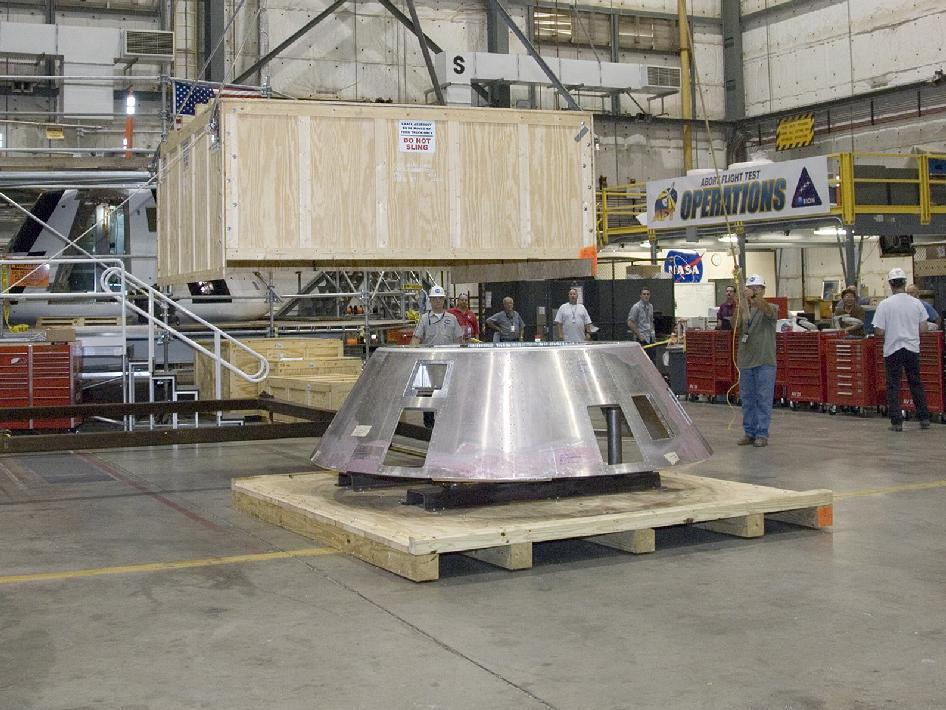 Crew removing the crate from the Forward Bay Cover for the Orion mockup crew module at Dryden Flight Research Center.