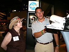 NASA engineer Tony Ginn shows the space shuttle to EAA AirVenture Museum volunteer Linda Meyers in the NASA 50th anniversary exhibit in the museum.