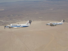 Two Beechcraft King Air mission support aircraft operated by NASA's Dryden Flight Research Center fly in formation over Rogers Dry Lake at Edwards AFB.