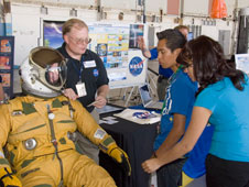 NASA Dryden flight surgeon Gregg Bendrick explains a high-altitude pressure suit to Palmdale High students Israel Morales and Ashley Moran.