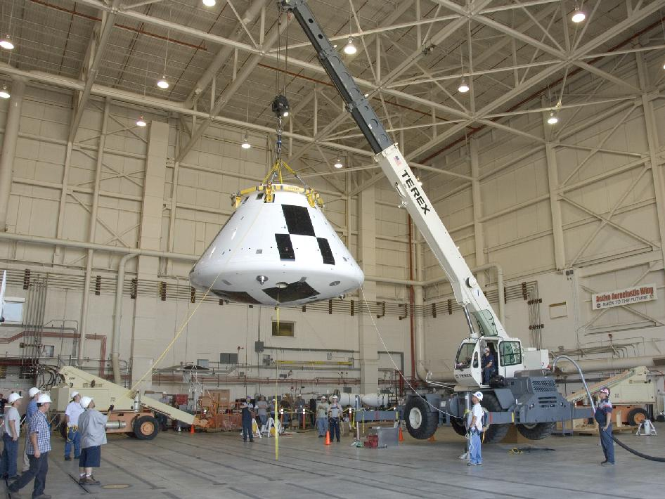 Orion pad abort crew module is lifted by a crane and placed on instrumented jacks