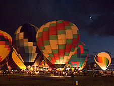 Balloons light up for the Balloon Glow, as a New Mexico moon appears from behind the clouds.