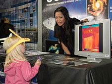 NASAs Darlene Mendoza shows a visitor to the SOFIA exhibit what she looks like through the lens of an infrared camera.