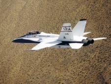 F-18B Systems Research Aircraft (SRA) in banked flight over southern California desert July 1998