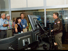 EAA members hear more about Global Hawk operations at the control room where the autonomously controlled aircraft is monitored. NASA pilot Mark Pestana, right, briefs the group.