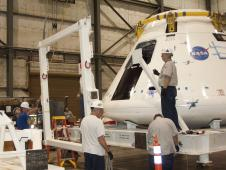 Technicians at NASA Dryden install the goalpost fixture to the Orion crew module integration stand during conversion of the stand into a transportation fixture for airlift of the module to the White Sands Missile Range in New Mexico.