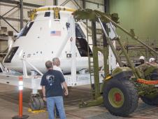 Technicians at NASA Dryden connect one of two mobilizer units to the Orion flight test crew module transportation fixture in preparation for loading the module onto an Air Force C-17 cargo aircraft for transport to the White Sands Missile Range in New Mexico.