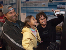 Tamera Eakes, 6, has her picture taken at a NASA photo kiosk with an assist from her dad Joseph and NASA exhibits staff member Kimberlee Buter.