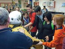 Students at Jackson Middle School in Albuquerque take the opportunity to see a high-altitude pressure suit up close.