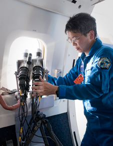 Hideyuki Tanno of the Japanese Aerospace Exploration Agency's Kakuda Space Center carefully aligns the twin lenses of his hand-held digital imaging cameras mounted in NASA's DC-8.