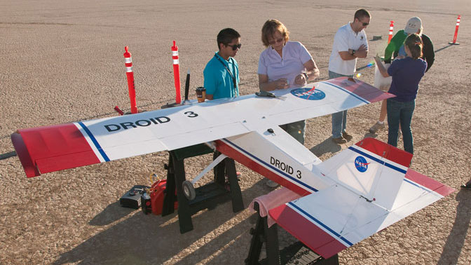 INSPIRE students and their mentors Leslie Monforton and Brian Taylor (second and third from left) prepare one of NASA Dryden's DROID large model aircraft for flight above Rosamond Dry Lake.