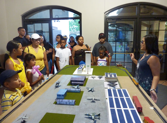 Informal education intern Mia Nilo, a biology major at San Diego State University, explains the Green Tech Airfield exhibit at the AERO Institute in Palmdale, Calif., to visitors during the Thursday Night on the Square activity in the Palmdale Civic Center.