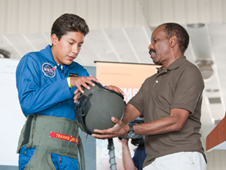 Bobby McElwain, right, assists Danny Medina with dressing in a flight suit.