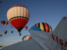 The nose of an inflatable half-scale model of a NASA F/A-18 in front of the NASA Aeronautics exhibit points skyward as a host of hot-air balloons ascend at the International Balloon Fiesta in Albuquerque.