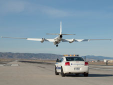 NASA's ER-2 high-altitude research aircraft is guided to a safe and smooth landing by voice commands radioed from an ER-2 mobile pilot driving a NASA Dodge Charger chase vehicle.