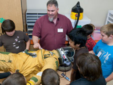 students observe full pressure suit used by pilots of high-altitude aircraft during a career day presentation.