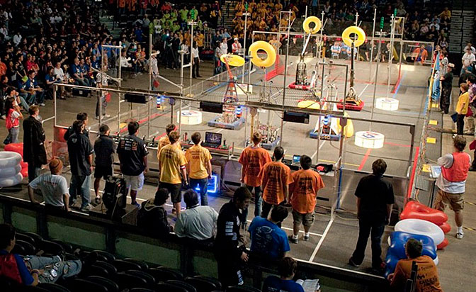 Yellow inflated doughnuts held high, robotics competing in the FIRST Robotics Competition scoot around the court.