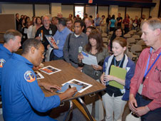 Discovery crewmembers sign autographs following their talk.