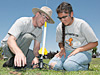 Biology professor Carl Kloock assists middle school student Guadalupe Lopez in mounting her rocket on the