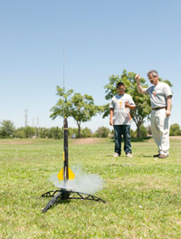 University official guides a student in setting up his rocket.