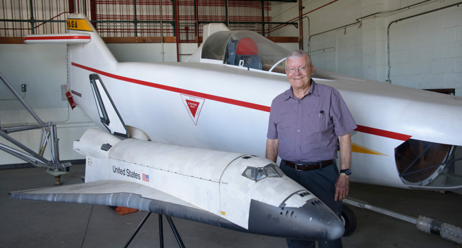 Retired NASA astronaut and research pilot Fred Haise of Apollo 13 fame with two of the vehicles from his 20-year career with NASA – a model of the space shuttle, and the restored M2-F1 lifting body that he flew when he was a research pilot at NASA Dryden Flight Research Center in the mid-1960s. Hais