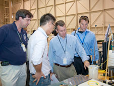 Patrick Chan, second from left, explains components of the Dryden-developed fiber optic strain-sensing technology to Bobby Braun, second from right. Also pictured are Tom Horn, left, and Robbie Schingler.