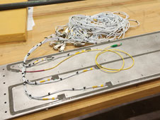 A single fiber optic cable, seen in yellow, replaces the need for all of the white bundle of wires.