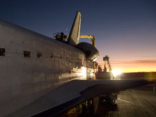 Floodlights cast long shadows over Endeavour as technicians prepare to tow the orbiter from the Edwards Air Force Base runway after landing on Nov. 30, 2008.